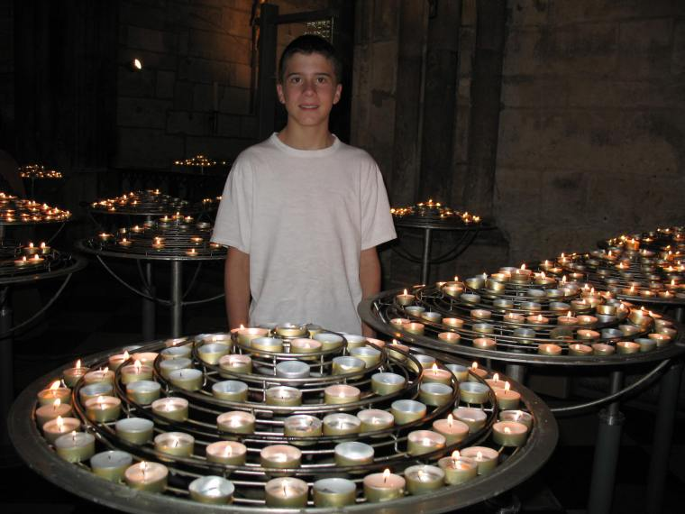 Adam in the midst of candles at Notre Dame Cathedral
