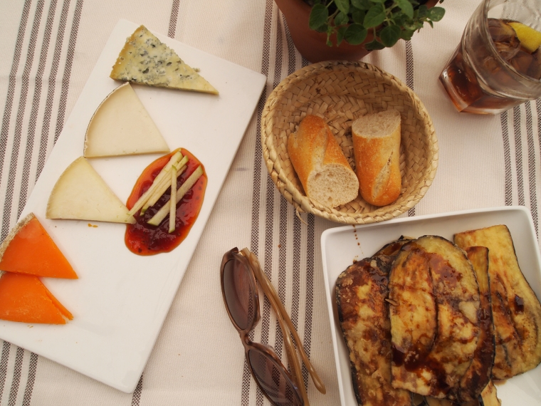 a cheese platter with tomato jam and fried eggplant drizzled with honey