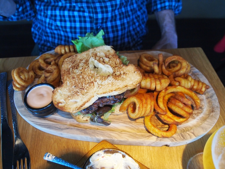 """Reindeer burger with """"Ljotur"""" blue & white cheese, herb mayonnaise, salad, peppers and tomato in brioche bread, served with fries"""