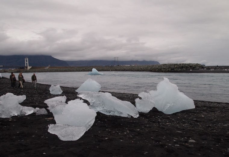 Glaciers rest on the black sand beach at the river mouth of Jökulsárlón
