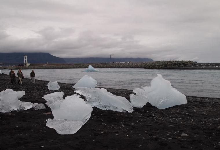 Glaciers rest on the black sand beach at the river mouth of Jökulsárlón